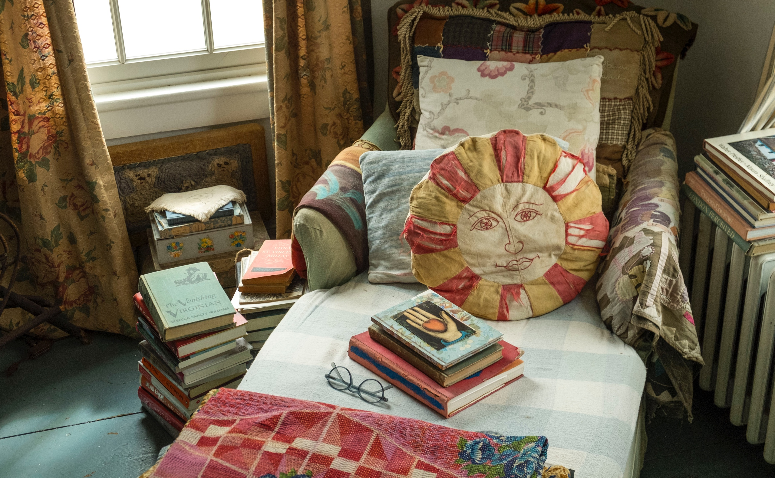 A cozy bedroom chaise surrounded by books and blanketed top-to-bottom with sun-faded coverlets, quilts, and textiles, softened with a collection of eclectic vintage pillows