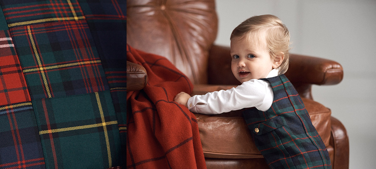 Baby boy wears tartan overalls over white long-sleeve bodysuit.